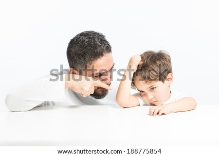 Father showing finger to his son to solve conflict between them - stock photo