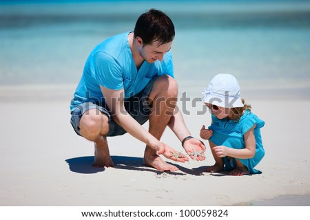 Father showing his little daughter two starfish - stock photo