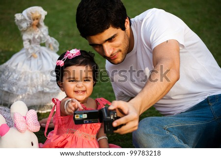 father showing pictures to his daughter on digital camera, biracial family - stock photo