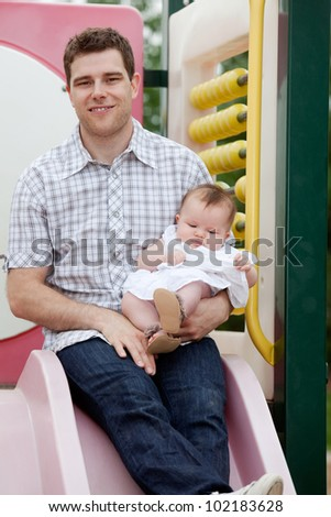 Father Sitting On Slide With His Adorable Daughter. - stock photo