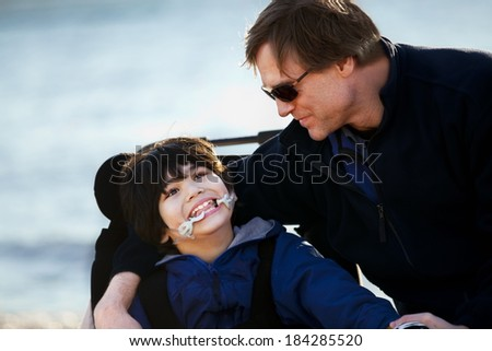 Father sitting with disabled son in wheelchair by lake shore - stock photo