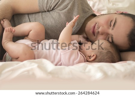 father sleeping with baby daughter - stock photo