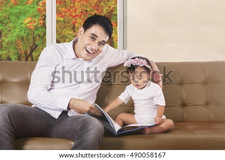 Father smiling at the camera and his daughter reading book on the brown couch, autumn on the window