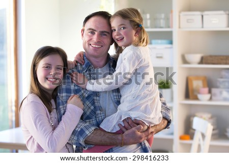 Father smiling for the camera with his daughters at home