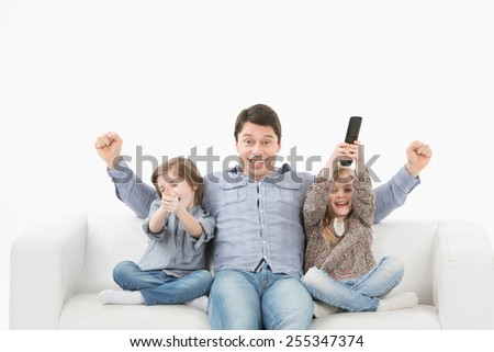 Father son and daughter watching television sitting on the couch on a white background - stock photo