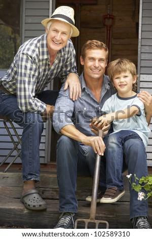 Father, son and grandson on veranda - stock photo