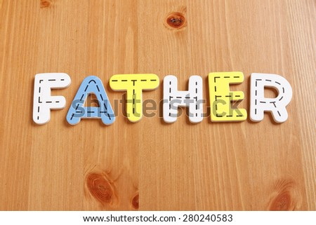 FATHER, spell by woody puzzle letters with woody background