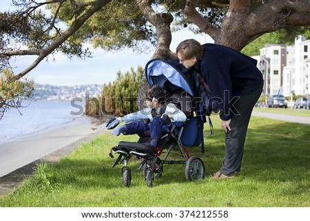 Father spending time with disabled son in wheelchair at the lake - stock photo