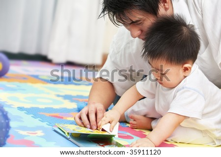 Father spending time with his little boy and tutoring him to learn reading
