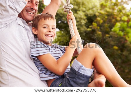 Father swinging with son at a playground - stock photo