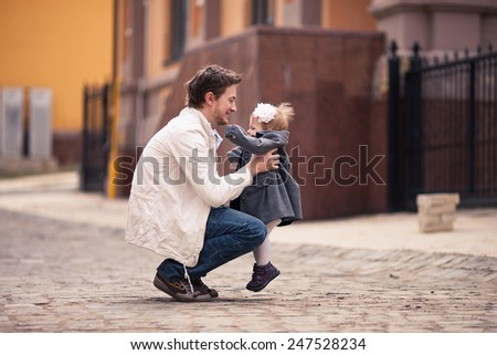 Father takes his little baby in his arms on the street with stone paving. Girl is dressed on grey coat and with white flower in hair. Young man dressed on white jacket and jeans. background diffused - stock photo