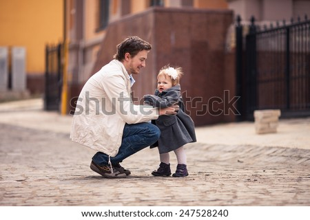 Father takes his little baby in his arms on the street with stone paving. Girl is dressed on grey coat and dress and with white flower in her hair. Young man dressed on white jacket and jeans - stock photo
