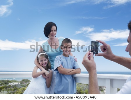 Father taking a portrait photo of happy family at vacation beach house balcony - stock photo