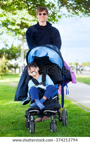 Father taking disabled son for a walk in wheelchair