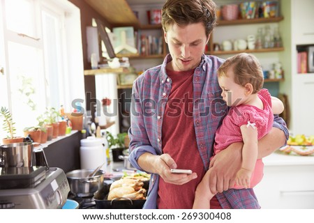 Father Taking Selfie On Mobile Phone Holding Young Daughter - stock photo
