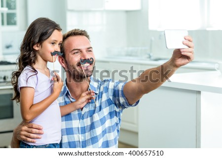 Father taking selfie with daughter holding artificial mustache stick at home - stock photo
