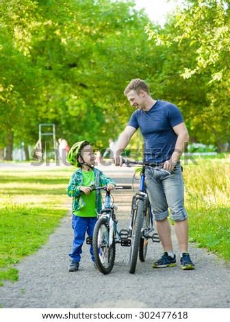 father talking with his son riding a bicycle in a park - stock photo