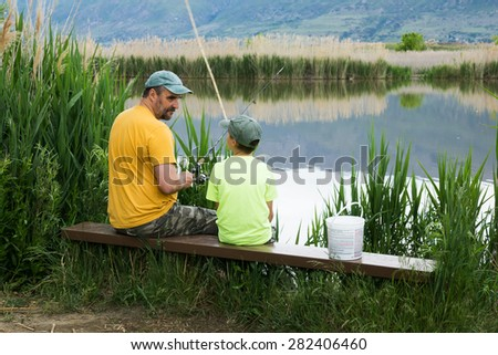 Father talks to son. Fishing on Bountiful Pond (Lake), Utah, US - stock photo