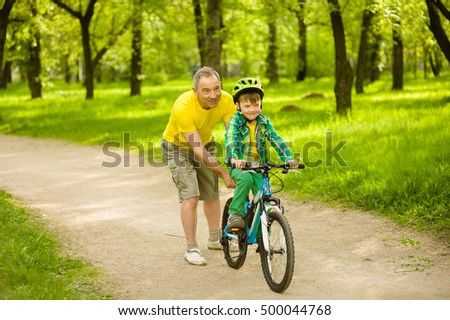 Father teaches his son to ride a bike