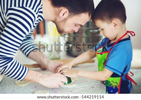 Father teaches son to cook. The man with the boy concocting dough.