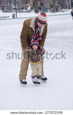 Father teaches son to skate at Boston Common Ice Skating Rink and Frog Pond, Boston, MA., New England, USA - stock photo