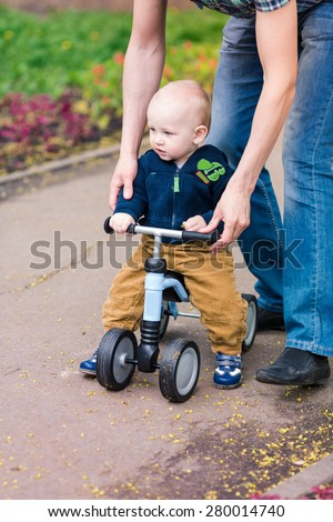 Father teaching baby boy how to ride on his first running bike - stock photo
