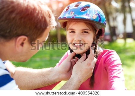 Father teaching brave daughter to ride bicycle putting on safety helmet - stock photo