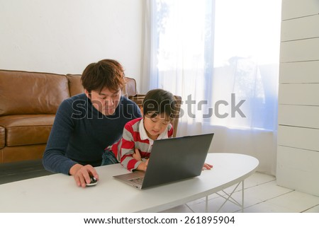 Father teaching child with a laptop