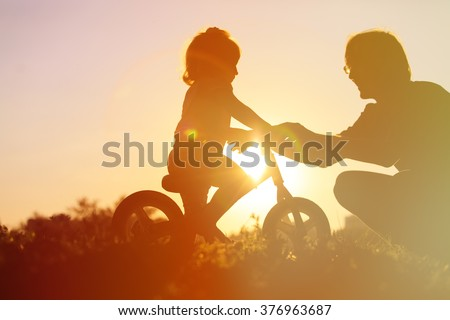 father teaching daughter to ride bike at sunset