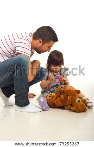 Father teaching his little daughter to use stethoscope  in their home - stock photo