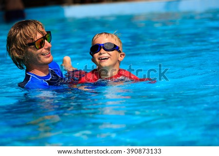 Father teaching his little son to swim