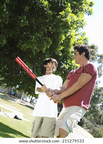 Father teaching son (10-12) how to hold baseball bat, standing on grass in park, smiling (tilt)