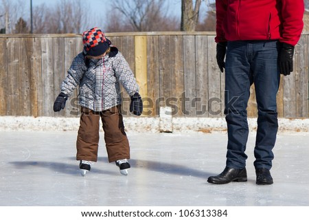 Father teaching son how to ice skate at an outdoor skating rink in winter. - stock photo