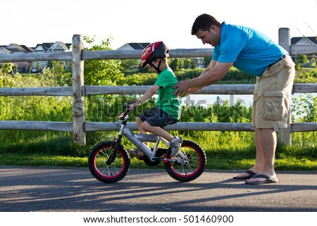 Father teaching son how to ride a bicycle
