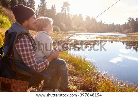 Father teaching son to fish sitting at lakeside - stock photo