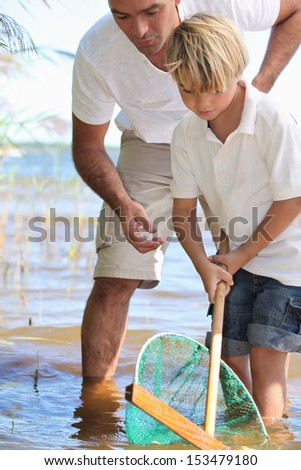 Father teaching son to fish with net - stock photo