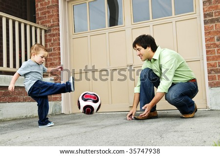 Father teaching son to play soccer on driveway - stock photo