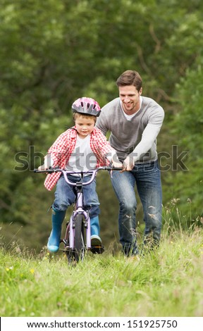 Father Teaching Son To Ride Bike In Countryside - stock photo