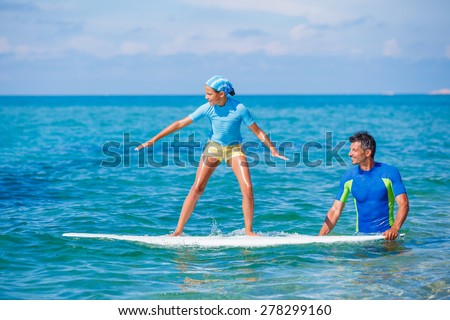 Father teaching surfing to his cute teen girl - stock photo