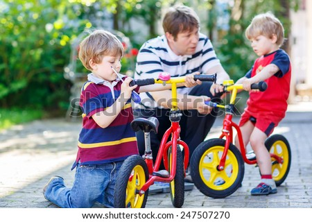 Father teaching two little kid boys to repair chain on bikes, showing to change a wheel. Family working together outdoors, on warm sunny day. Active leisure with kids. - stock photo