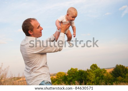 Father throwing baby boy against blue sky - stock photo