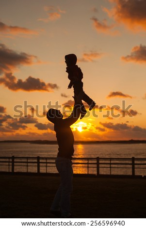 Father throwing his kid up in the air on the beach, silhouette shot on sunset - stock photo