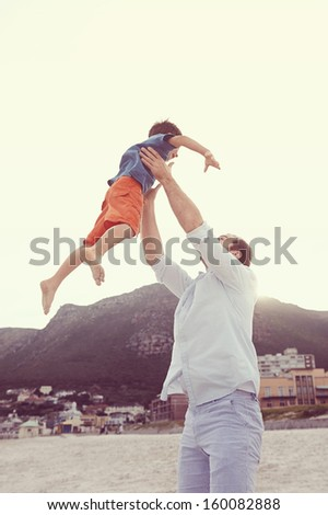 Father throwing son in air at beach having fun playful laughing dad - stock photo
