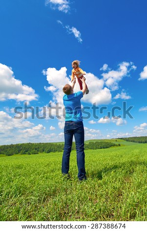 Father throws daughter up in the air in the summer park - stock photo