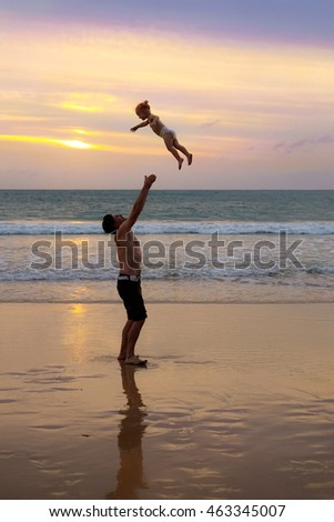 Father throws his daughter high in the air at the beach near the sea at the spectacular cloudy sunset