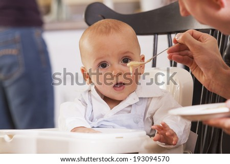 Father trying to get his baby boy to eat with spoon of food