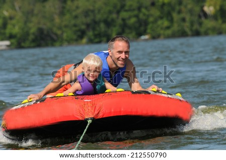 father tubing with his young son behind a boat - stock photo