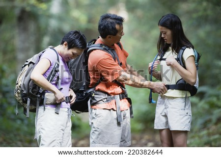 Father tying his daughter's backpack - stock photo
