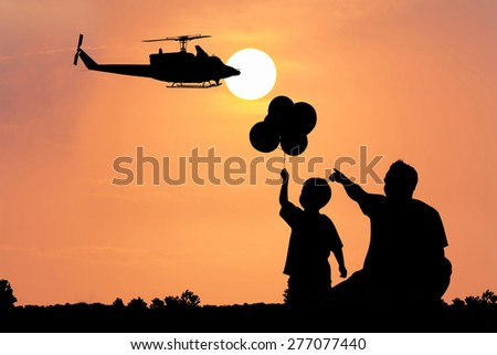 father use hand point to  the helicopter on the sky at sunset his son see - stock photo