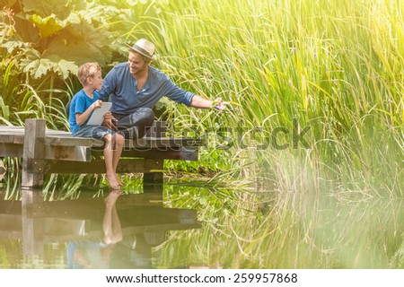 father using a digital tablet to teach to his young boy the beauties of the nature, they are sitting on a wooden pontoon on a river in summertime - stock photo
